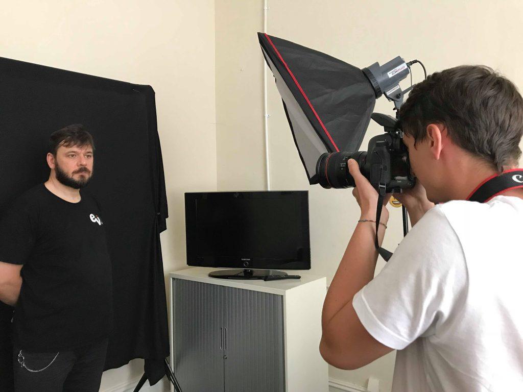 Liam, volunteer, taking photos at a staff photo shot.
